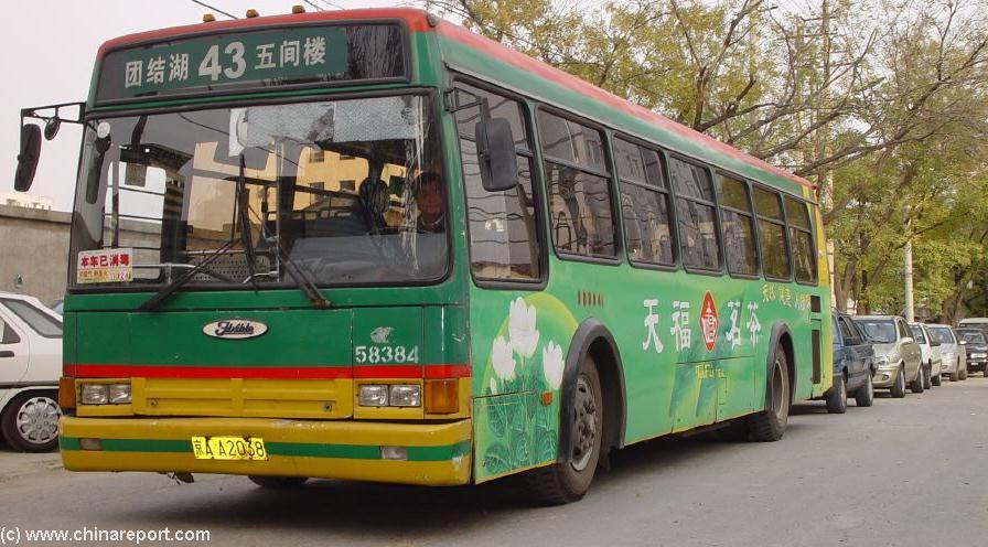 Inside a beijing bus the lady with the bright colored outfit is the